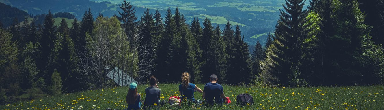 Family sitting in the grass with a view of the mountains.