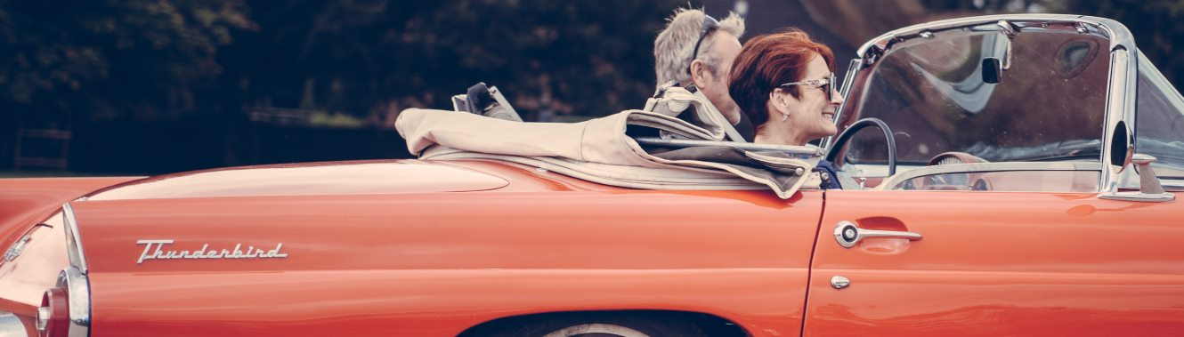 Mature couple driving in a red convertible car.
