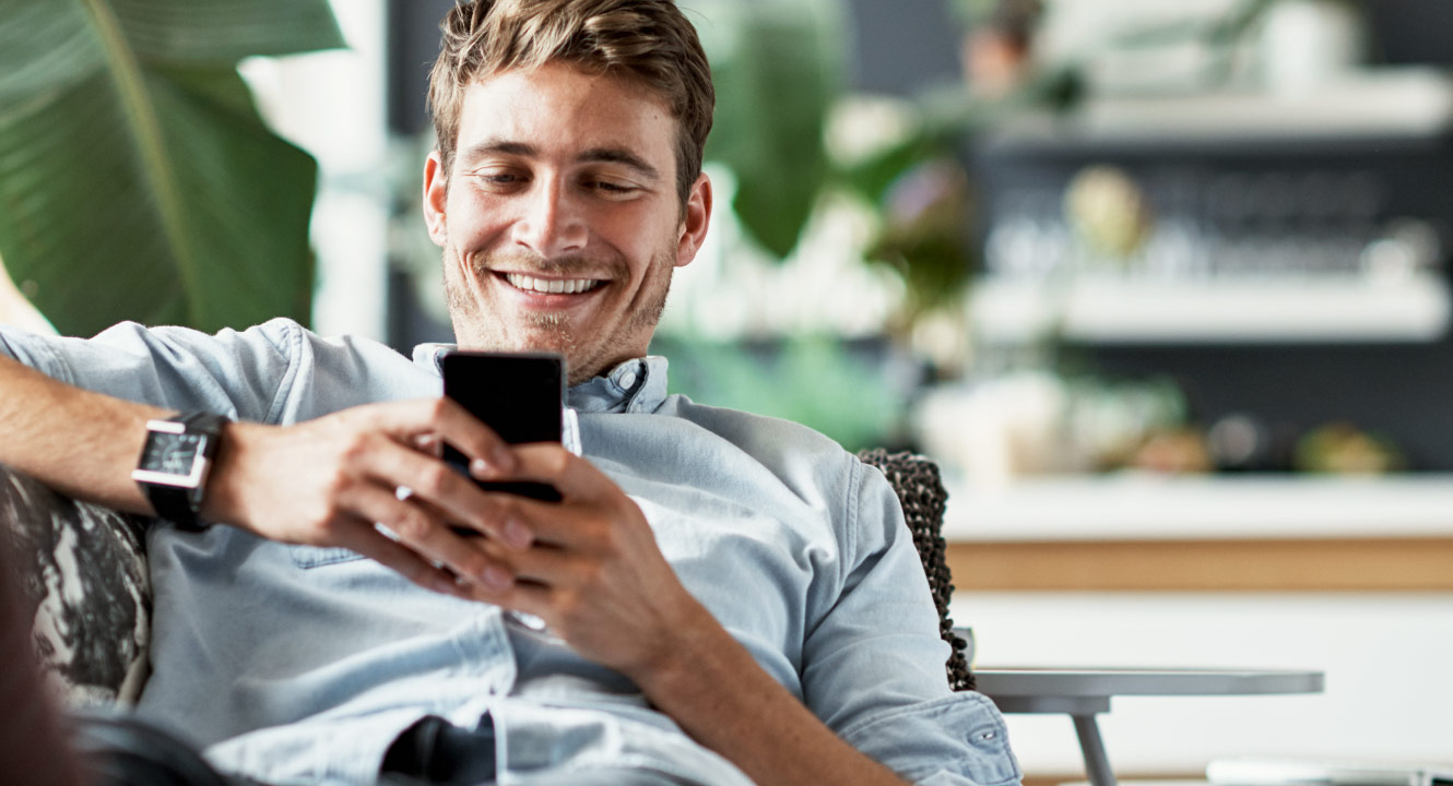 A man looking at his mobile phone and smiling